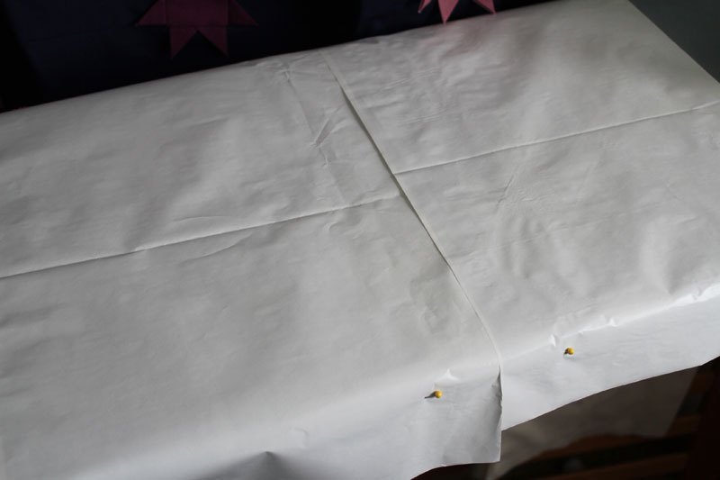 pin pressing paper to ironing board